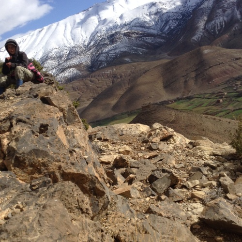 10 year old sitting on a ledge of rocks way, way far up a mountain with a village below and snow capped mountains behind him.